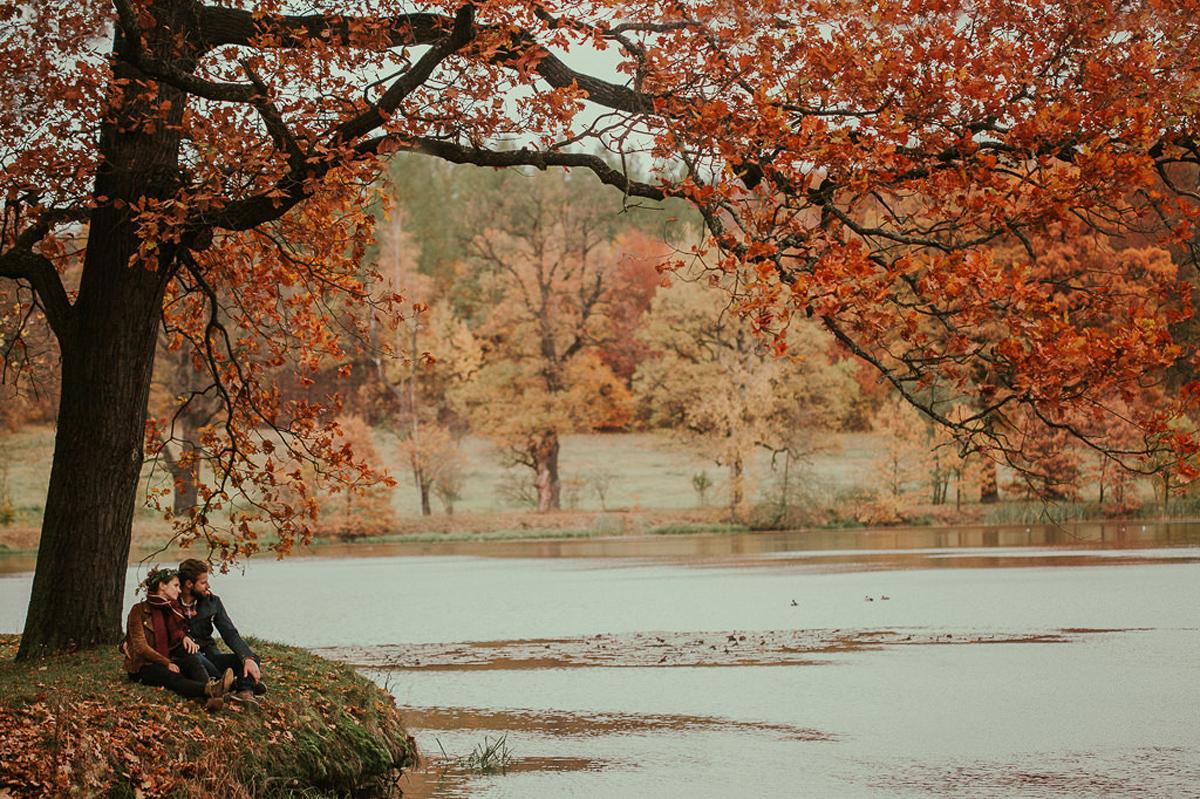 obraz pary nad jeziorem wsrod jesiennych drzew