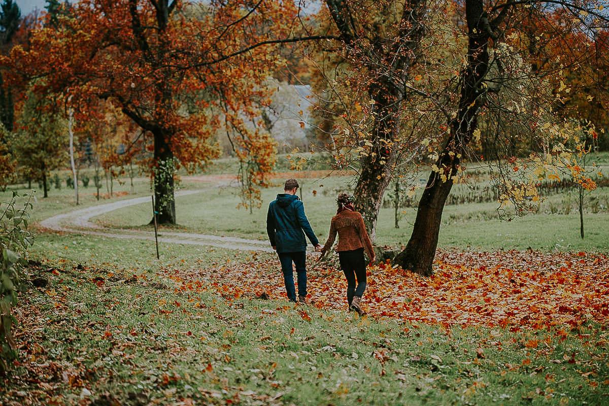 jesienna sesja dla zakochanych para idąca po opadłych liściach